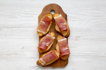 Crostini with serrano ham on wooden board on white wooden table, top view. Flat lay, overhead, from above.