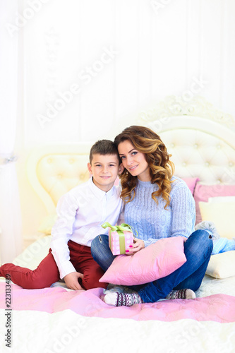 Young Mother Sitting With Son And Gift On Bed Concept Of Celebrating Birthday Childhood