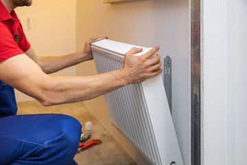 man installing room heater on the wall