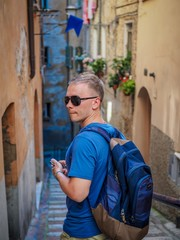 A young blond man turned around on the ancient street of Perugia in the Umbria region, on his shoulders he carries a backpack