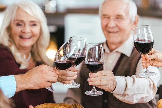 senior couple clinking glasses with family during holiday celebration