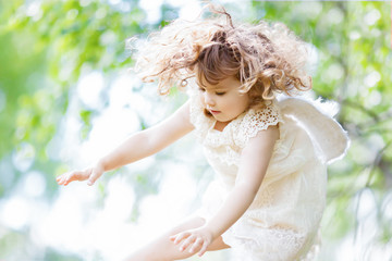 Beautiful little Angel girl flying at the forest