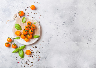 Organic Cherry Orange Rapture Tomatoes on the Vine with basil and pepper on chopping board on stone kitchen background. Space for text