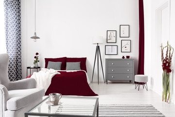 Glamour bedroom interior in white, gray and burgundy with a bed dressed in wine color linen. Lamp and drawer cabinet by the bed. Real photo.
