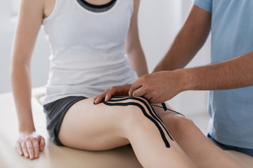 Close-up on physiotherapist putting tapes on patient's leg during kinesiotaping