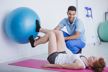 Smiling physiotherapist supporting woman exercising with rehabilitation ball