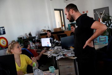 Journalists of Hungary's main independent website Index talk in the newsroom in Budapest