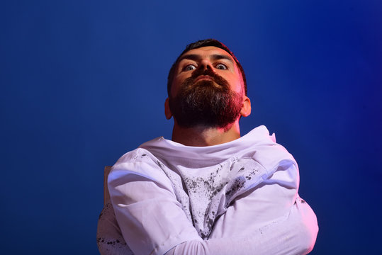 Insane mad in straitjacket on blue background. 31 october. Make up and scary concept for man. Celebration party.