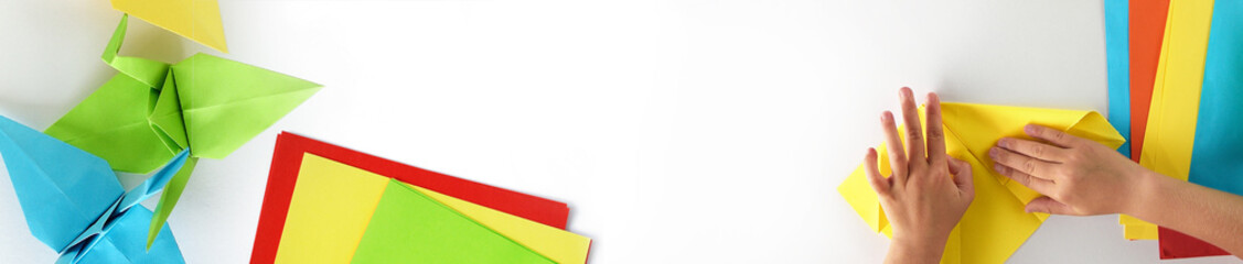 Web banner, origami kids.  Color cranes of origami from paper on a white background