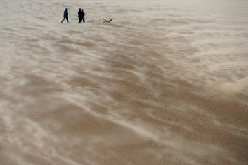 People walk along the beach through blowing sand in New Brighton
