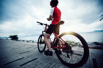 Woman cyclist use mobile phone while riding Mountain Bike on seaside