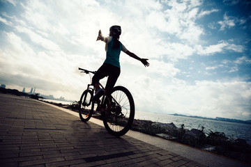 Woman cyclist hands free cycling riding Mountain Bike on sunrise seaside