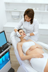 Skin Care. Pregnant Woman On Face Cleansing At Beauty Clinic
