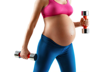 Close up of pregnant woman with beautiful healthy body holding dumbbells isolated on white background. Concept of healthy life