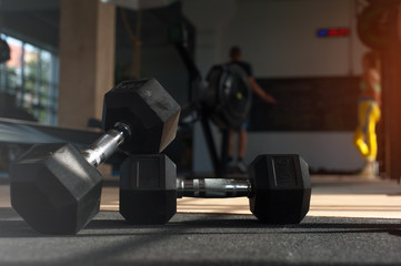 Workout with dumbbells. Blurred gym background.