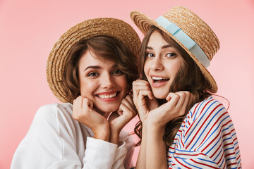 Women friends posing isolated over pink background.