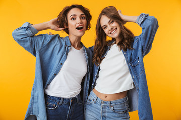 Women friends posing isolated over yellow background.