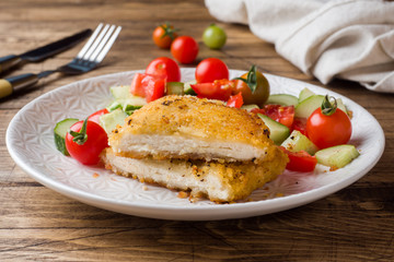 Chicken cutlet and cucumber salad with tomatoes on a wooden table