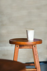 Hot coffee in paper cup place on the brown wooden chair