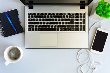 Gray wooden office desk table with laptop computer, smartphone,notebook, pen and cup of coffee. Top view. Copy space. Flat lay.