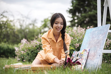 Picture of semiling concentrated young asian female artist sitting at home garden with painting accessories, holding tube of oil paint, mixing colors on palette; unfinished painting on canvas near her