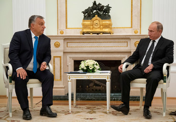 Russian President Putin listens to Hungarian PM Orban during their meeting at the Kremlin in Moscow