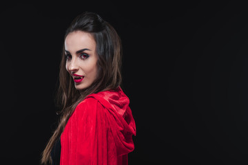 sexy vampire woman in red cloak isolated on black
