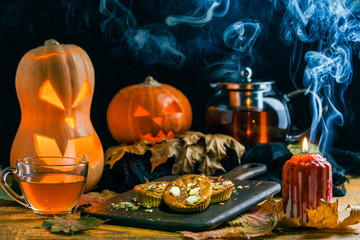 Halloween photo of table with pumpkin, biscuit, burning candle