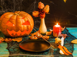 Halloween image of table with pumpkin, burning candle,