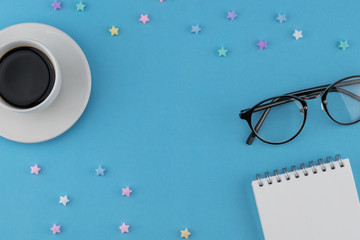 A cup of coffee, blank notebook and eyeglasses decorate with pastel star pattern on blue background with copy space