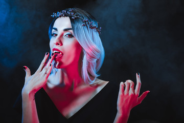 vampire woman licking blood from fingers on dark background with smoke