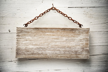 wooden signboard hanging on a chain