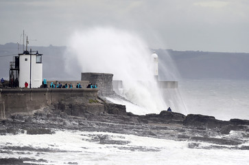 Waves crash over the lighthouse at Porthcawl, Wales, Britain,