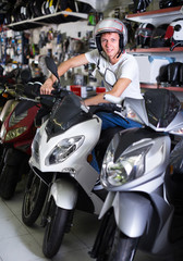Person in helmet is sitting on motorbike
