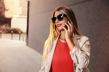 Closeup portrait of beautiful young business woman talking on the phone outdoors