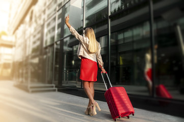 Successful Young business woman with suitcase going into sunset