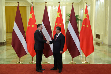 Latvia's President Raimonds Vejonis shakes hands with China's President Xi Jinping at The Great Hall Of The People in Beijing, China