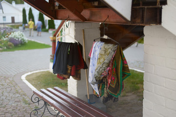 Shawls and bedspreads hang before the entrance to the Orthodox church. Religion, traditions and rules.