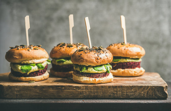 Flat-lay of healthy vegan burgers with quinoa beetroot patties, avocado cream and green sprouts on wooden board, grey wall at background. Vegetarian, clean eating, alkiline diet food