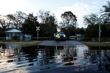 People take cell phone photos of the flood waters in the aftermath of Hurricane Florence in Fair Bluff