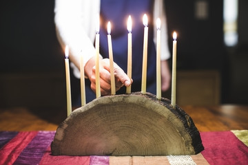 Woman lighting wooden menorah