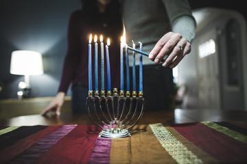 Man and woman lighting menorah