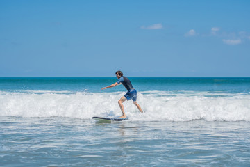 Young man, beginner Surfer learns to surf on a sea foam on the Bali island