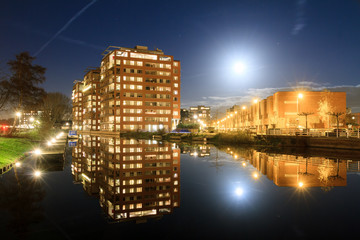Modern new residential district in Leiden, The Netherlands, with apartment buildings reflected in the water at night, with a full moon