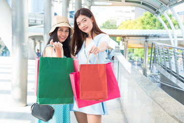 Beautiful young Asian woman and friend is standing at shopping mall with a colored shopping bag in hand and happy after shopping.
