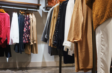 Women's and clothes, dresses and shirts on hangers and shelves in a modern clothing store.
