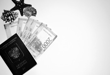 Passport on the background of money and seashells. Vacation at sea. Money from different countries.  Russian banknotes. Two thousand rubles. Metal ancient coins.  Travel credit. Savings and deposits.