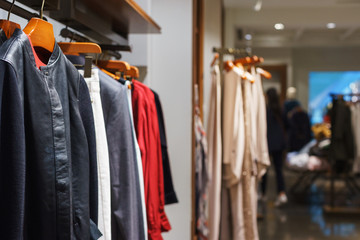 Fashionable men's and women's clothing on wooden hangers in a modern clothing store.