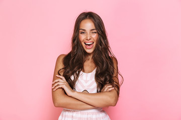 Image of cute woman 20s with long hair wearing dress smiling at camera with arms crossed, isolated over pink background