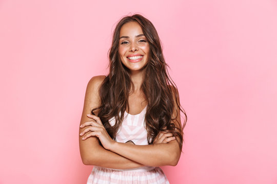 Image of european lovely woman 20s with long hair wearing dress smiling at you with arms crossed, isolated over pink background